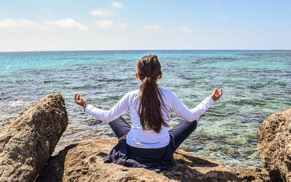 Young Girl Doing Yoga at Ocean